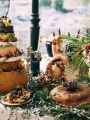 The Buffet Table At The Festival Is A Makeshift Cheese Cake. The Table Is Decorated With Olive Branches And Leaves.